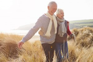 older couple walking though a field laughing together